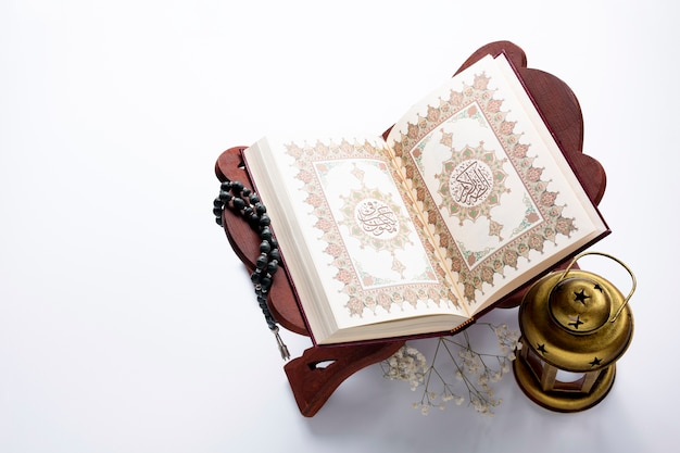 High angle opened quran next to candle Free Photo