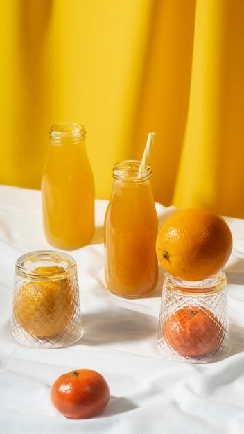 Succo d'arancia ad alto angolo nella disposizione delle bottiglie Foto Gratuite