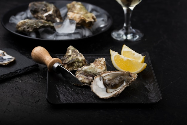 High angle of oysters on plate with knife and lemon slices Free Photo