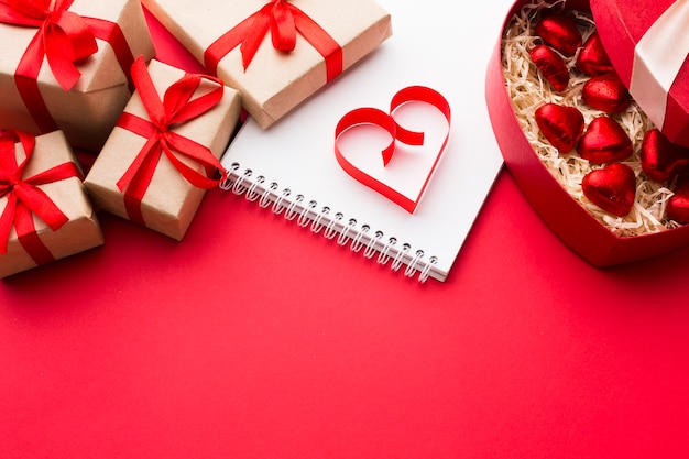 High angle of paper heart shape with presents and sweets Free Photo