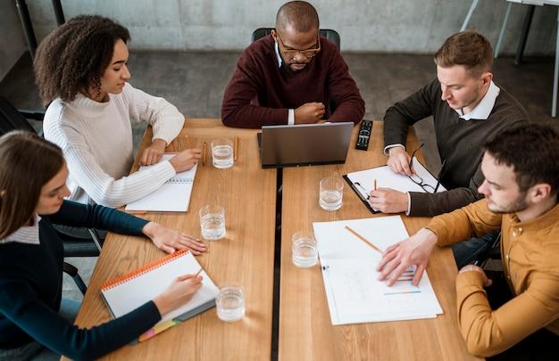 Elevato angolo di persone al tavolo in ufficio durante una riunione Foto Gratuite