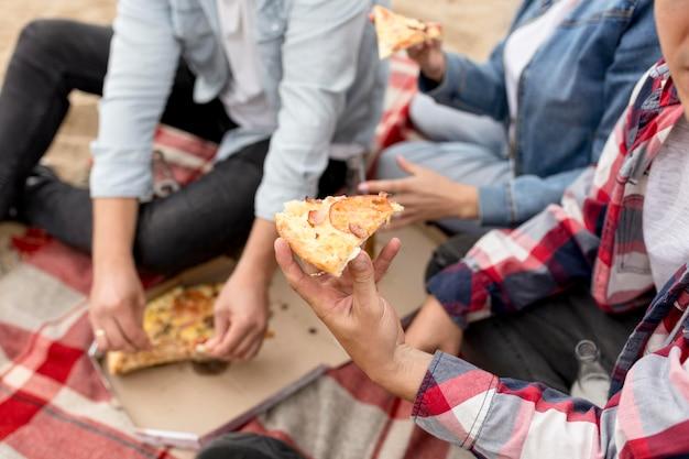 Люди под высоким углом берут кусок пиццы Бесплатные Фотографии