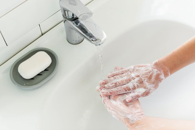 High angle of person washing hands at the sink Free Photo