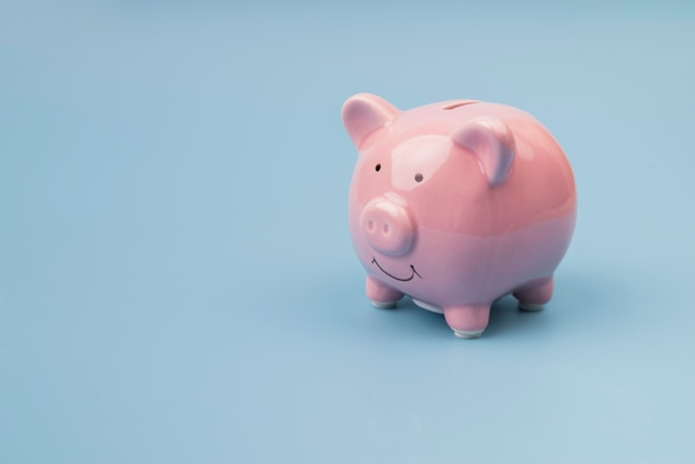 High angle piggy bank on blue background Free Photo