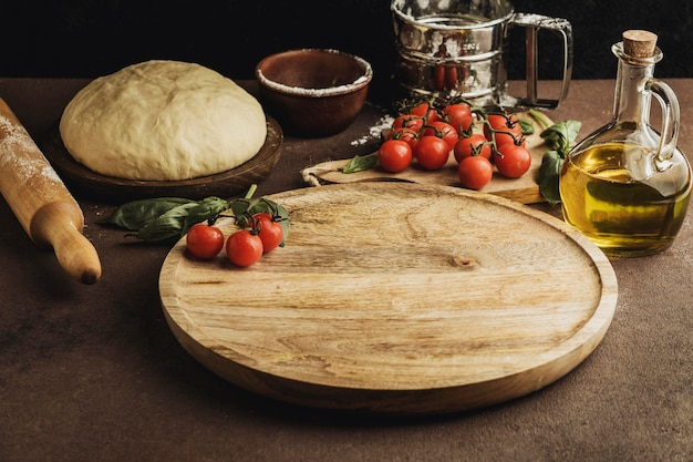 High angle of pizza dough with wooden board and tomatoes Premium Photo