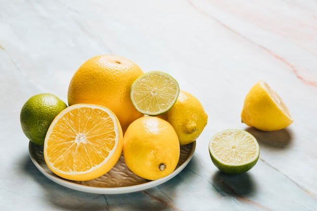 High angle of plate with lemon on marble background Free Photo