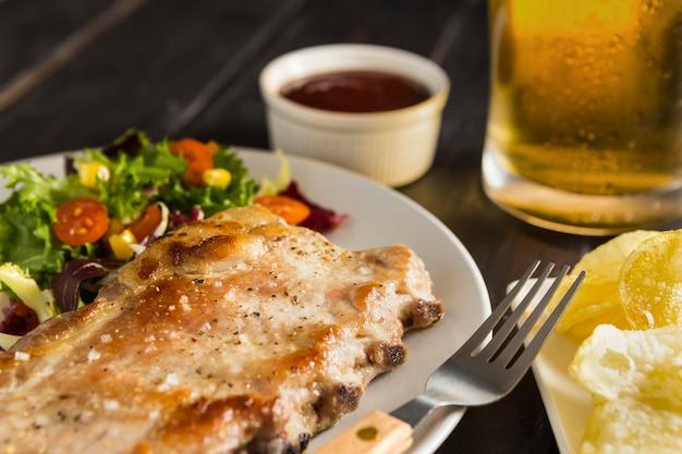 Angolo alto del piatto con bistecca e birra Foto Gratuite
