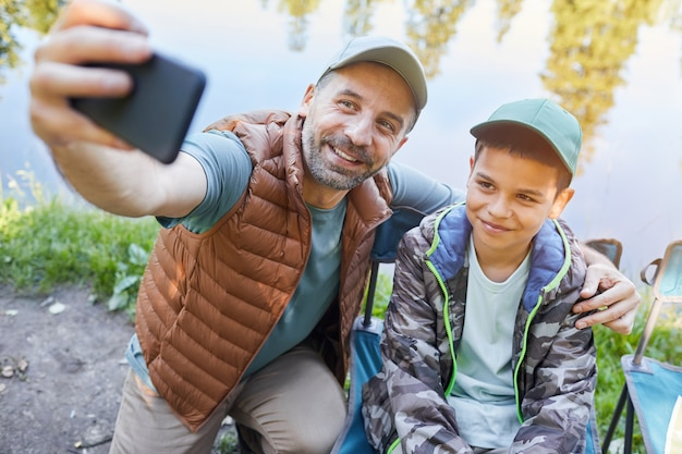 High angle portrait of loving father and son taking selfie photo via smartphone while enjoying camping trip together Premium Photo