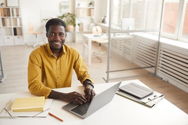 노트북을 사용하고 최소한의 사무실 인테리어에서 작업을 즐기면서 카메라를보고 웃는 아프리카 계 미국인 남자의 높은 각도 초상화, 복사 공간 프리미엄 사진