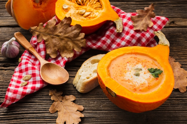 High angle pumpkin bisque and wooden spoon with ingredients and leaves Free Photo