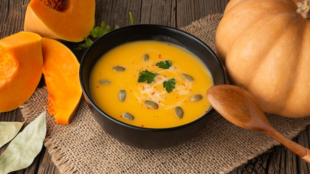 High angle pumpkin soup in bowl with pumpkin and wooden spoon Free Photo