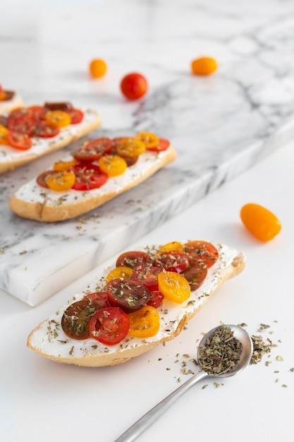 Panini ad angolo alto con crema di formaggio e pomodori sul bancone in marmo Foto Gratuite