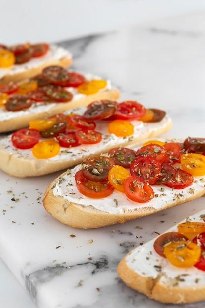 Panini ad angolo alto con crema di formaggio e pomodori su marmo Foto Gratuite