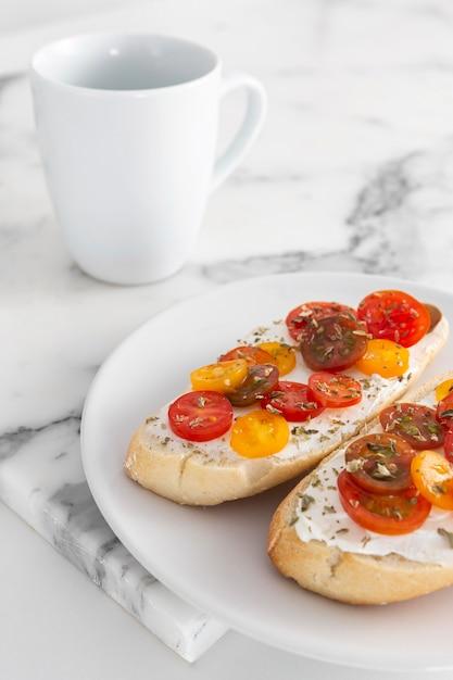 Panini ad angolo alto con crema di formaggio e pomodori con tazza Foto Gratuite