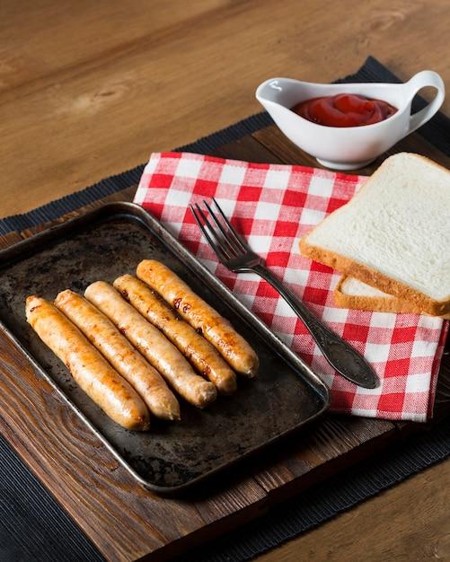 パンとトレイのハイアングルソーセージ 無料写真