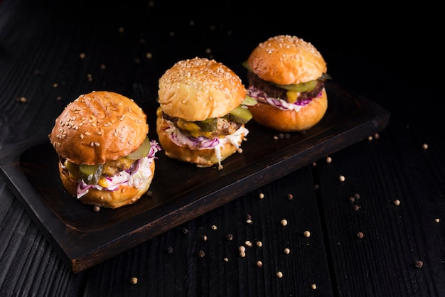 High angle set of burgers on a wooden board Free Photo