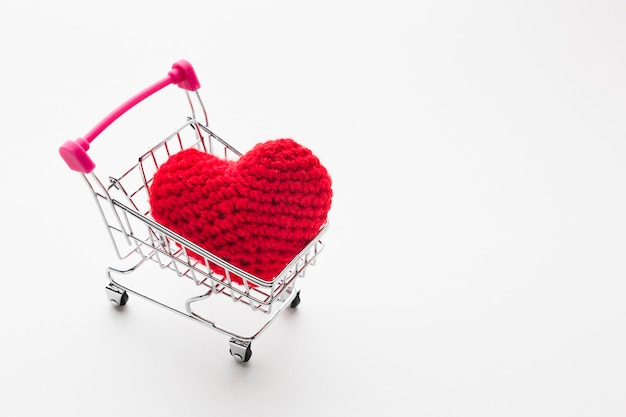 High angle of shopping cart with valentines day ornament Free Photo