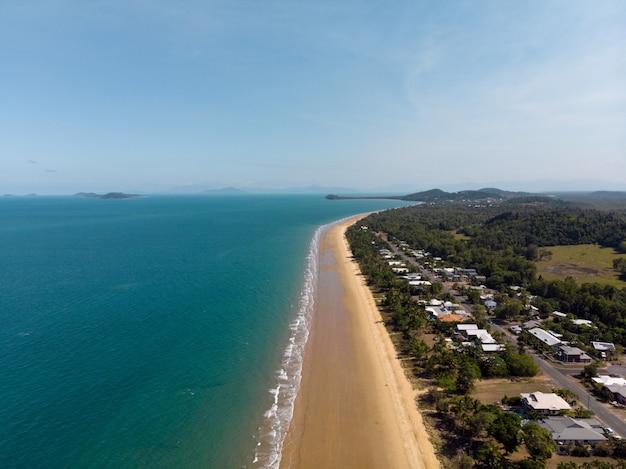 Inquadratura dall'alto di una spiaggia con una piccola città sulla riva Foto Gratuite