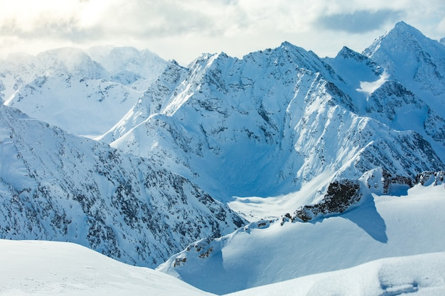 High angle shot of a beautiful mountain range covered with snow under the cloudy sky Free Photo