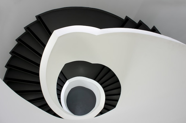 High angle shot of a black stairway going down surrounded by white walls Free Photo