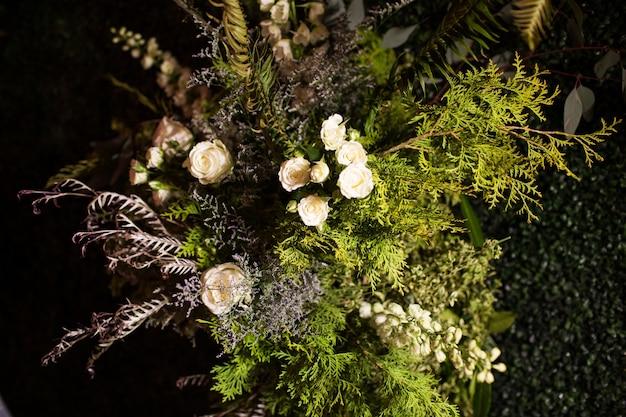 Colpo di alto angolo di un bouquet con foglie sempreverdi e rose bianche sotto le luci Foto Gratuite