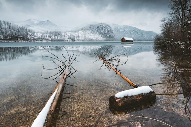 Colpo di alto angolo di un lago calmo con colline sotto un cielo nebbioso Foto Gratuite