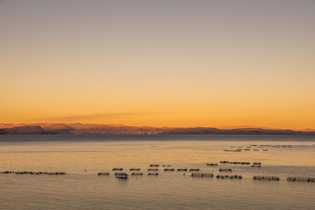 Colpo di alto angolo della superficie calma dell'oceano con le montagne Foto Gratuite