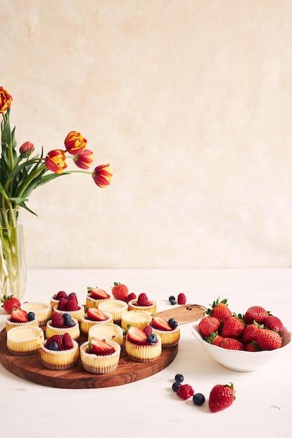 Colpo di alto angolo di cupcakes al formaggio con gelatina di frutta e frutta su un piatto di legno Foto Gratuite