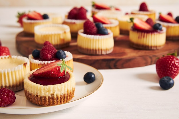 High angle shot of cheese cupcakes with fruit jelly and fruits on a wooden plate Free Photo