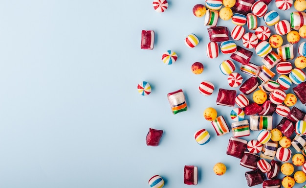 High angle shot of colorful candies on a light blue background Free Photo