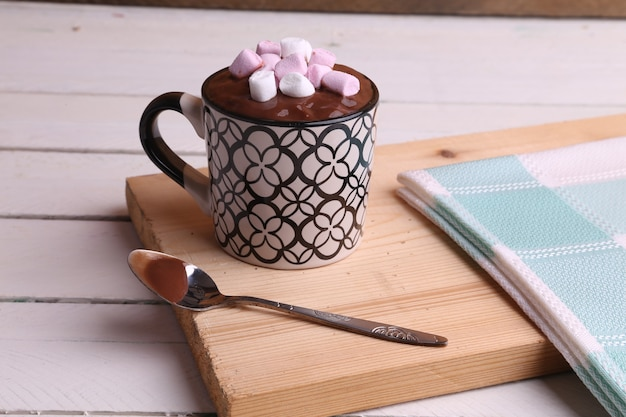 High angle shot of a cup of hot chocolate with marshmallows on a wooden surface Free Photo