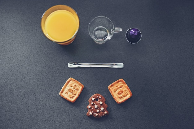 High angle shot of delicious cookies and glass cups with juice and water on a grey surface Free Photo