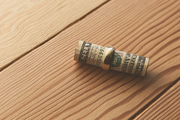 Colpo di alto angolo di banconote da un dollaro arrotolate in un anello d'oro su una superficie di legno Foto Gratuite