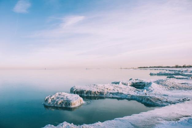 Colpo di alto angolo della riva congelata del mare in inverno sotto il cielo calmo Foto Gratuite