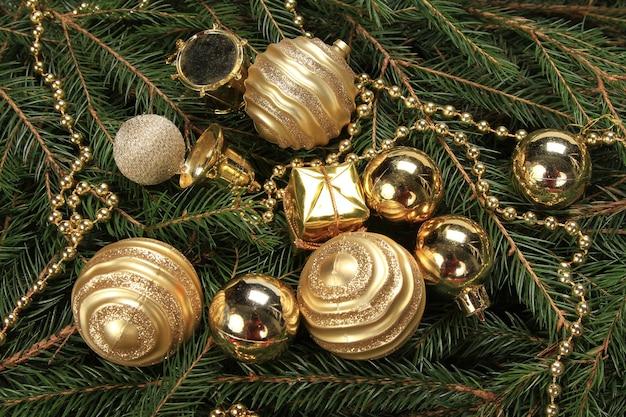 Colpo di alto angolo di palline dorate con perline su rami di abete Foto Gratuite