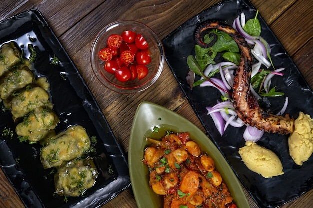 High angle shot of a grilled octopus and potatoes with different vegetables Free Photo
