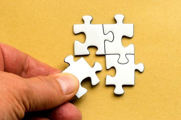 Colpo di alto angolo di una mano umana che attacca un pezzo del puzzle al resto Foto Gratuite