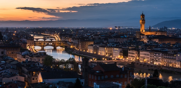 Colpo di alto angolo di un sacco di edifici con luci e un ponte di sera Foto Gratuite