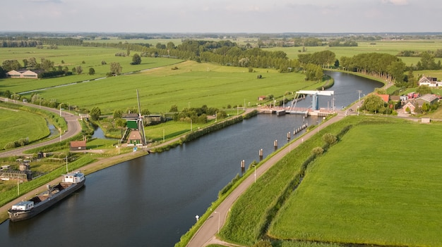 High angle shot of the merwede canal surrounded by grassy fields captured in nehterlands Free Photo