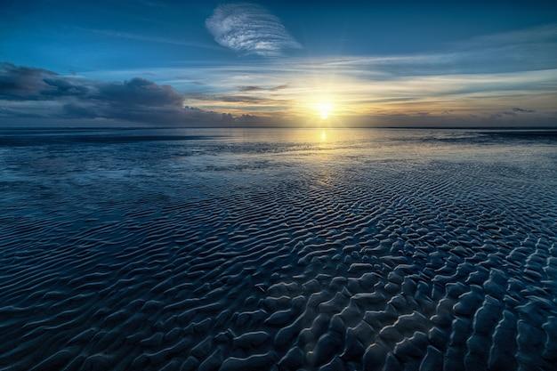 Colpo di alto angolo dell'acqua dell'oceano e del sole che splende all'orizzonte Foto Gratuite