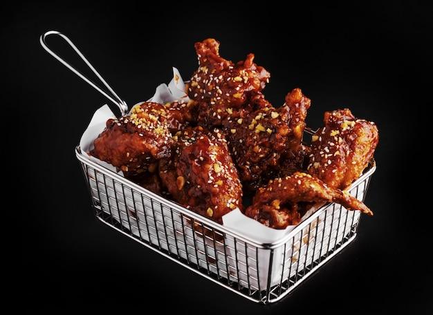 검은 표면에 매운 소스와 함께 맛있는 프라이드 치킨 바구니의 높은 각도 샷 무료 사진