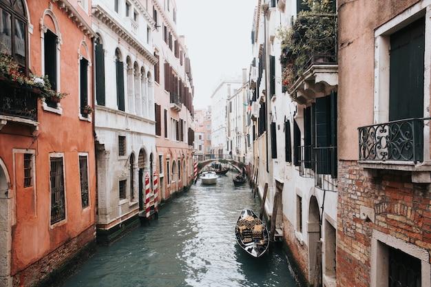 2つの建物の間にゴンドラがあるヴェネツィアの美しい運河のハイアングルショット 無料写真
