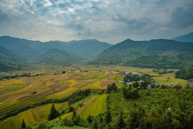 Высокий угол выстрела красивый зеленый пейзаж с высокими горами и дома под грозовыми облаками Бесплатные Фотографии