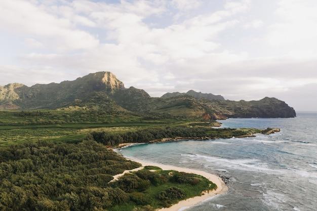 Снимок красивого берега моря с белым облачным небом под высоким углом Бесплатные Фотографии