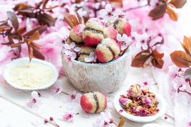 小さな花に囲まれたおいしいビーガンピーチクッキーのボウルのハイアングルショット 無料写真