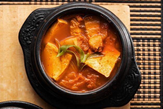 木製のテーブルの上においしい野菜とジャガイモのスープのボウルのハイアングルショット 無料写真
