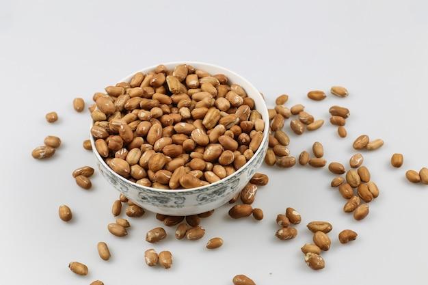 Снимок миски с арахисом на белой поверхности под высоким углом Бесплатные Фотографии
