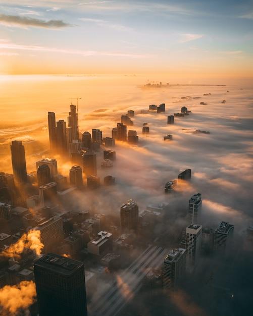 Снимок городского пейзажа с высокими небоскребами во время заката, покрытого белыми облаками, под высоким углом Бесплатные Фотографии