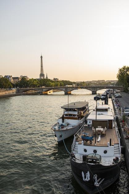 Высокий угол снимка пришвартованной яхты на реке с эйфелевой башней Бесплатные Фотографии