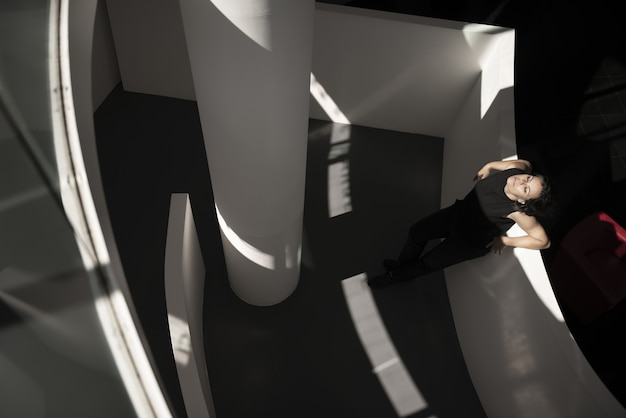 검은 바닥이있는 건물의 흰 벽에 기대어 여성의 높은 각도 샷 무료 사진